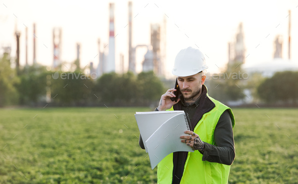 Young engineer with smartphone standing outdoors by oil refinery. Copy space - Stock Photo - Images
