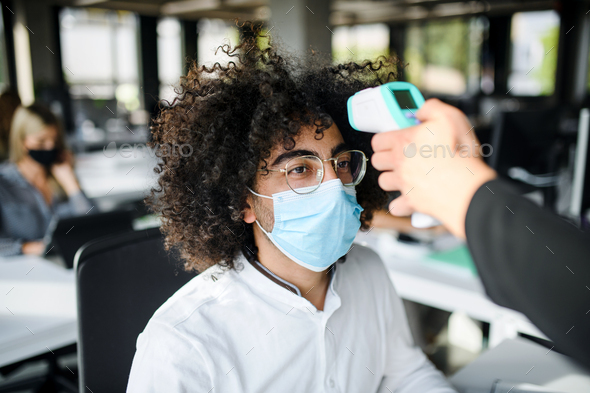 Young man with face mask back at work in office after lockdown, measuring temperature - Stock Photo - Images
