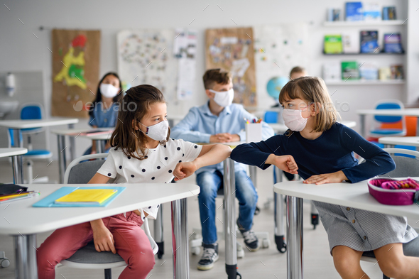 Children with face mask back at school after covid-19 quarantine and lockdown, greeting - Stock Photo - Images