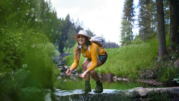 Happy young woman standing by stream on a walk outdoors in summer nature - Stock Photo - Images