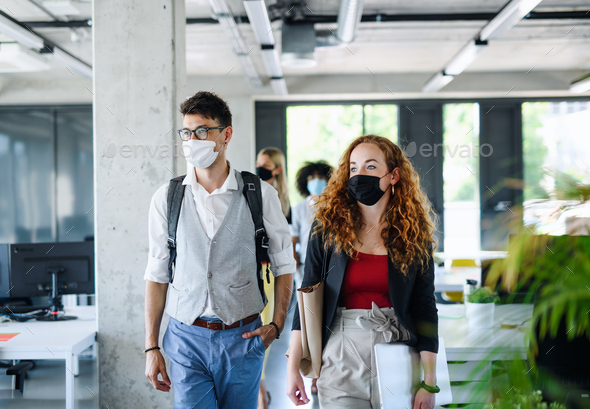 Young people with face masks back at work in office after lockdown, walking - Stock Photo - Images