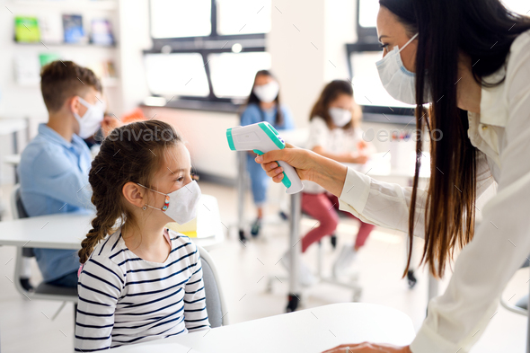 Teacher, child with face mask at school after covid-19 quarantine, measuring temperature - Stock Photo - Images