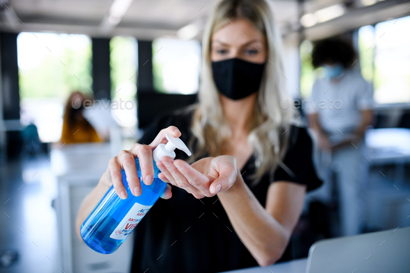 Young woman with face mask back at work in office after lockdown, disinfecting hands - Stock Photo - Images