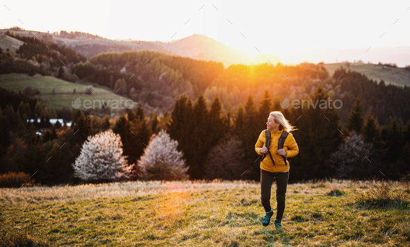 Front view of senior woman hiker walking outdoors in nature at sunset - Stock Photo - Images