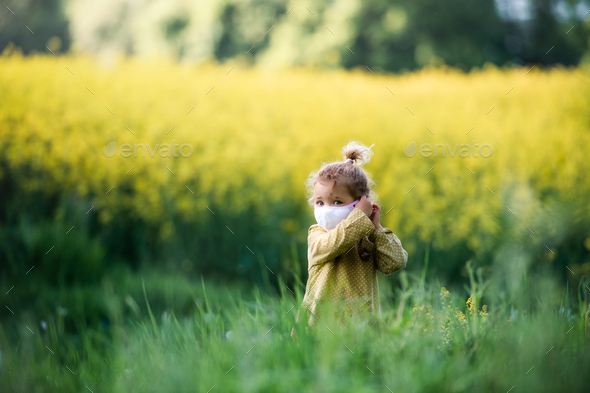 Front view of small toddler girl with face mask standing in nature in rapeseed field - Stock Photo - Images