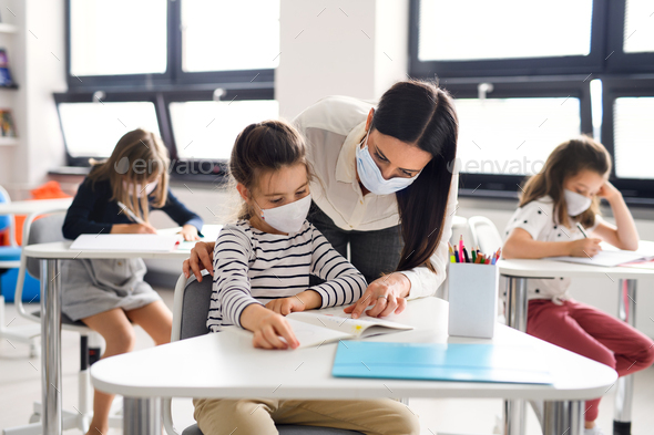Teacher and children with face mask back at school after covid-19 quarantine and lockdown - Stock Photo - Images