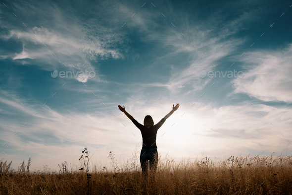 Young happy woman in a golden field on sunset. - Stock Photo - Images