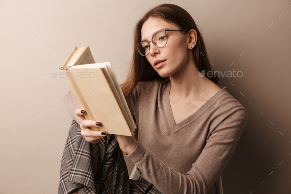 Photo of charming serious woman reading book and sitting on chair - Stock Photo - Images