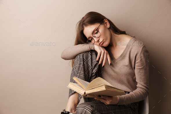 Photo of charming sad woman reading book and sitting on chair - Stock Photo - Images
