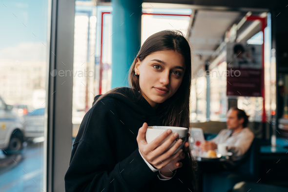 Close up portrait of pretty female drinking coffee - Stock Photo - Images