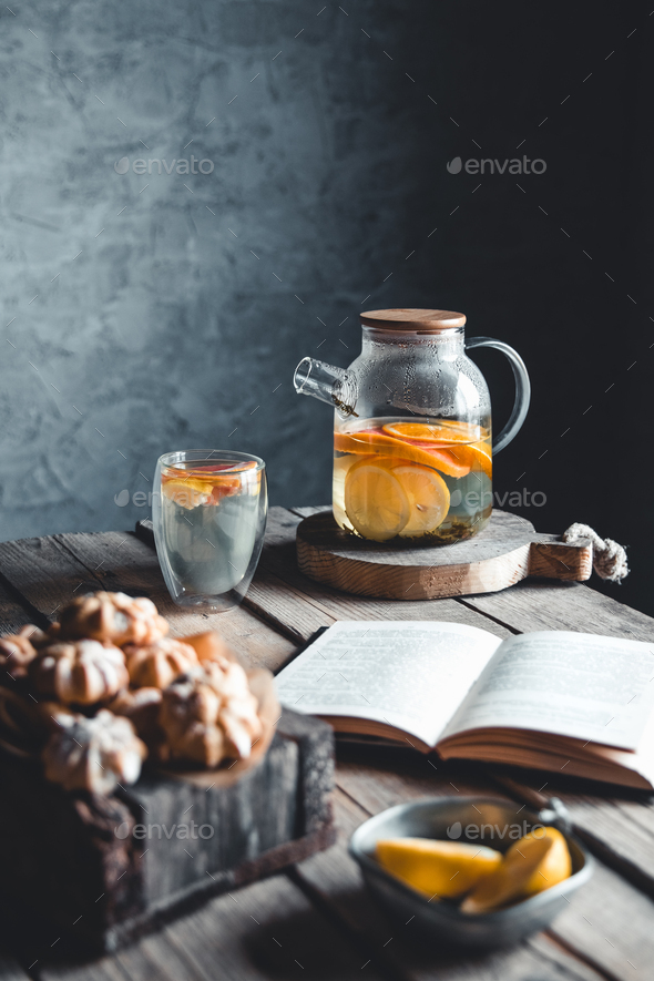 A book with citrus tea is waiting in a vintage kitchen. Rest, hobbies, education, read - Stock Photo - Images