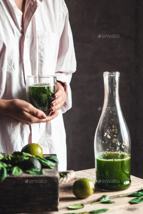 Woman takes a glass of smoothie into a glass, detox, wholesome food, vegan, eco. Body cleansing - Stock Photo - Images
