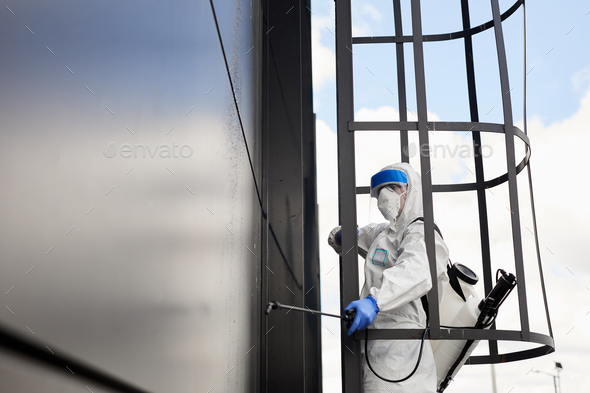 Worker Disinfecting Black Facade - Stock Photo - Images
