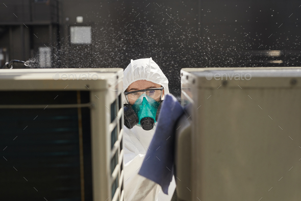 Female Worker Disinfecting Equipment Outdoors - Stock Photo - Images