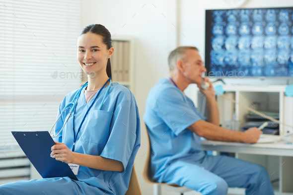 Smiling Female Nurse Holding Clipboard in Hospital - Stock Photo - Images