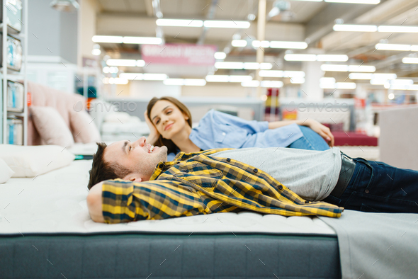 Love couple lying in bed, furniture store showroom - Stock Photo - Images
