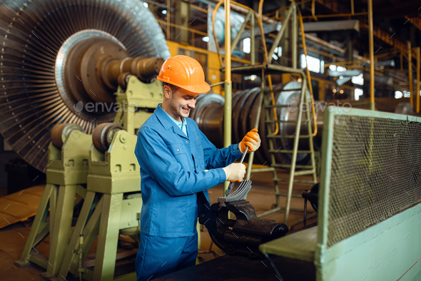Engineer works with turbine detail on factory - Stock Photo - Images