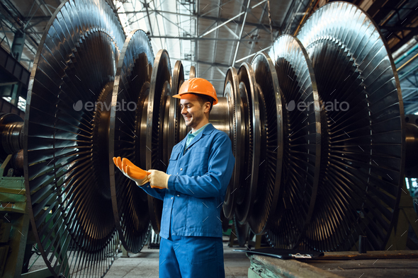 Worker checks turbine impeller vanes on factory - Stock Photo - Images