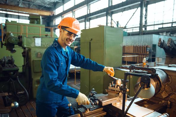Male worker checks turning lathe on plant - Stock Photo - Images