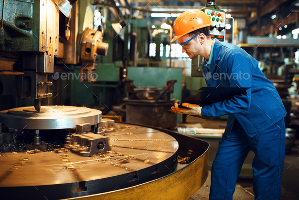 Turner stanging at the automated lathe, factory - Stock Photo - Images