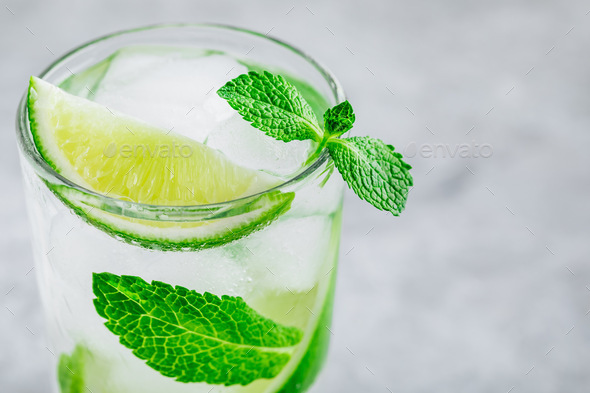 Mojito cocktail with ice, fresh mint and lime in glass on gray stone background. - Stock Photo - Images