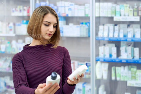 Woman choosing medical products in drugstore - Stock Photo - Images