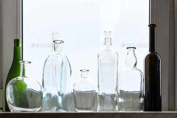 many empty drunk bottles on home window sill - Stock Photo - Images