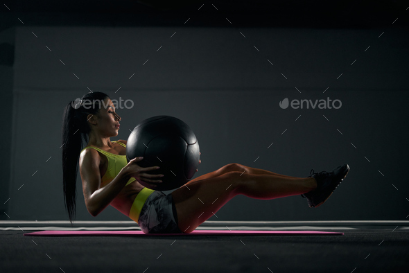 Sportswoman training abs with ball in gym - Stock Photo - Images