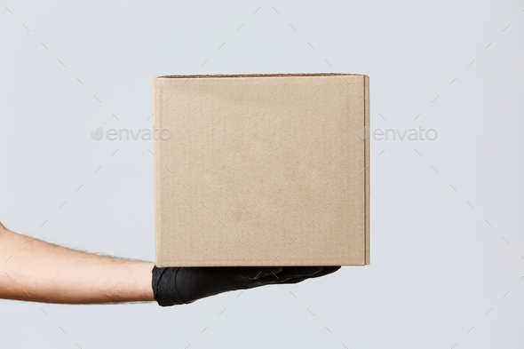 Contactless delivering, covid-19 and shopping concept. Image of courier hand in rubber gloves - Stock Photo - Images