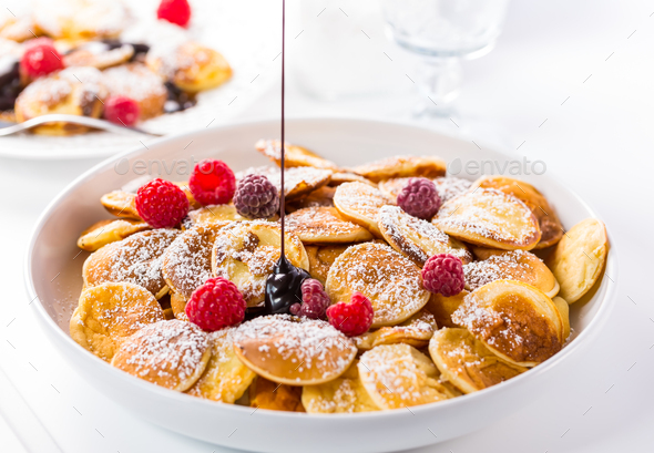 Poffertjes - small Dutch pancakes with fresh raspberries - Stock Photo - Images