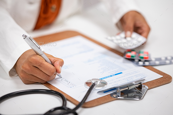 Doctor writing and checking medical prescription - Stock Photo - Images