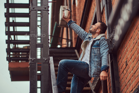 A handsome stylish man wearing a denim jacket holding a takeaway coffee on stairs outside. - Stock Photo - Images