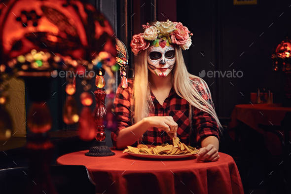 Young blonde girl with undead makeup in flower wreath eating nachos at a mexican restaurant. - Stock Photo - Images