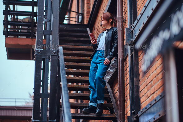 Beautiful hipster girl wearing trendy clothes sitting on stairs outside the cafe - Stock Photo - Images