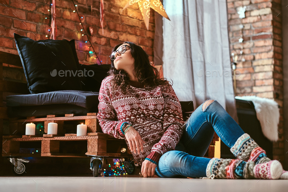 Cheerful beautiful girl sitting on a couch with gift boxes in a decorated room with loft interior. - Stock Photo - Images