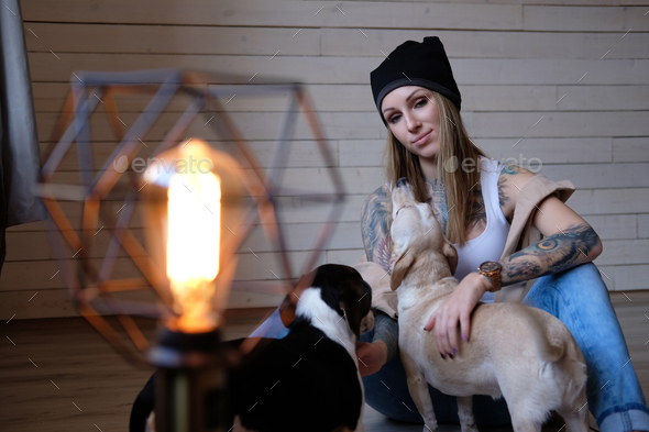 Portrait of a hipster tattoed girl playing with her little dogs while sitting on a wooden floor. - Stock Photo - Images