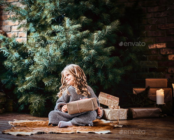 Cute little girl with blonde curly hair sitting on a floor next to the christmas tree - Stock Photo - Images