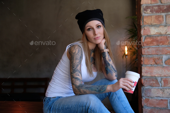 Portrait of a tattooed blonde hipster girl in a room with loft interior - Stock Photo - Images