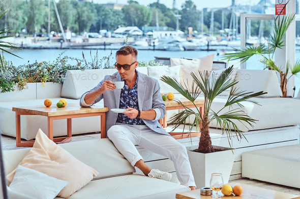 Successful man in modern elegant clothes at outdoor cafe against the background of city wharf. - Stock Photo - Images