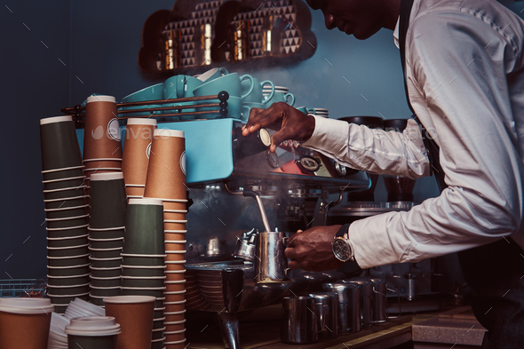 Side View of African American barista in white shirt and apron making coffee with a coffee machine. - Stock Photo - Images