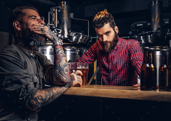 Tattooed hipster male with stylish beard and hair drinking beer sitting at the bar counter - Stock Photo - Images