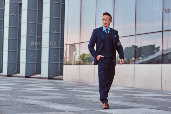 Confident businessman dressed in an elegant suit standing outdoors against cityscape background. - Stock Photo - Images