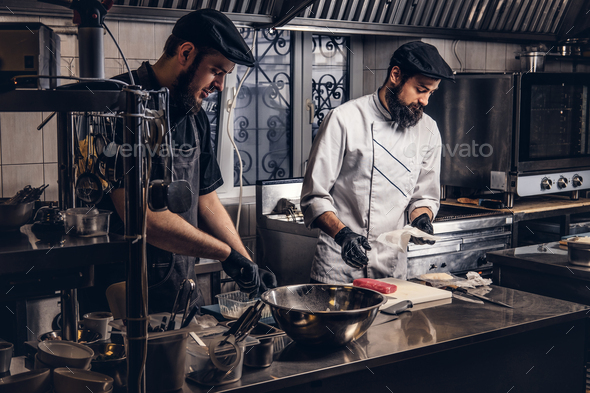 Two brutal cooks dressed in uniforms preparing sushi in a kitchen. - Stock Photo - Images