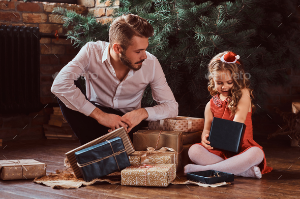 Dad and daughter sitting on a floor surrounded by gifts next to the Christmas tree at home. - Stock Photo - Images