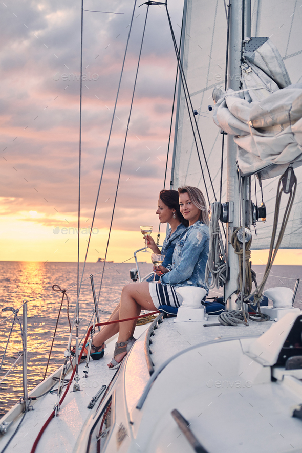 Two female friends drink wine and relaxing on the yacht, during sunset on the high seas. - Stock Photo - Images