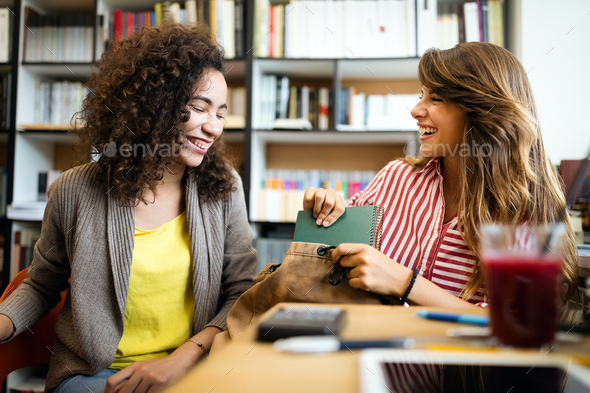 University students in cooperation at library. Group of young friends reading books - Stock Photo - Images