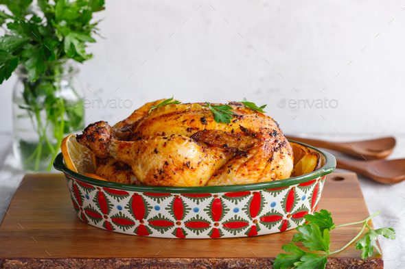 Whole roasted chicken with fresh parsley and lemon wedges in a festive dish - Stock Photo - Images