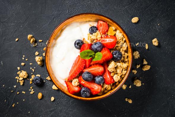 Greek yogurt granola with fresh berries on black stone table - Stock Photo - Images