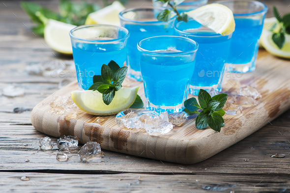 Blue curacao liqueur with lemon on the wooden table - Stock Photo - Images