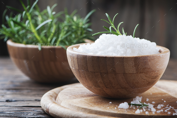 Sea salt and green rosemary on the wooden table - Stock Photo - Images